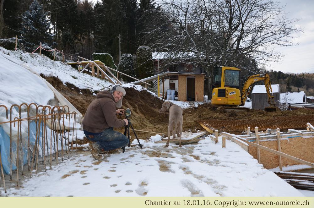 Mesure au niveau laser de la hauteur des fondations - Pita surveille l'avancée des travaux.