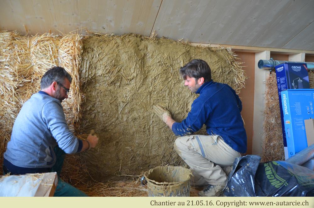 14.05.2016 Kevin et Marc posent la couche d'adhérence (argile pure) sur les bottes de paille lors du premier chantier participatif.