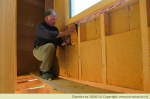 18.06.16 Yves insère de la laine de bois dans l'ossature bois. Celle-ci remplace la paille lorsque l'espace disponible n'est pas suffisant.